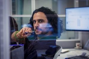 A man staring through a cubicle.